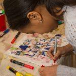A young girl makes art at an activity table at East Liberty Celebrates MLK 2015.
